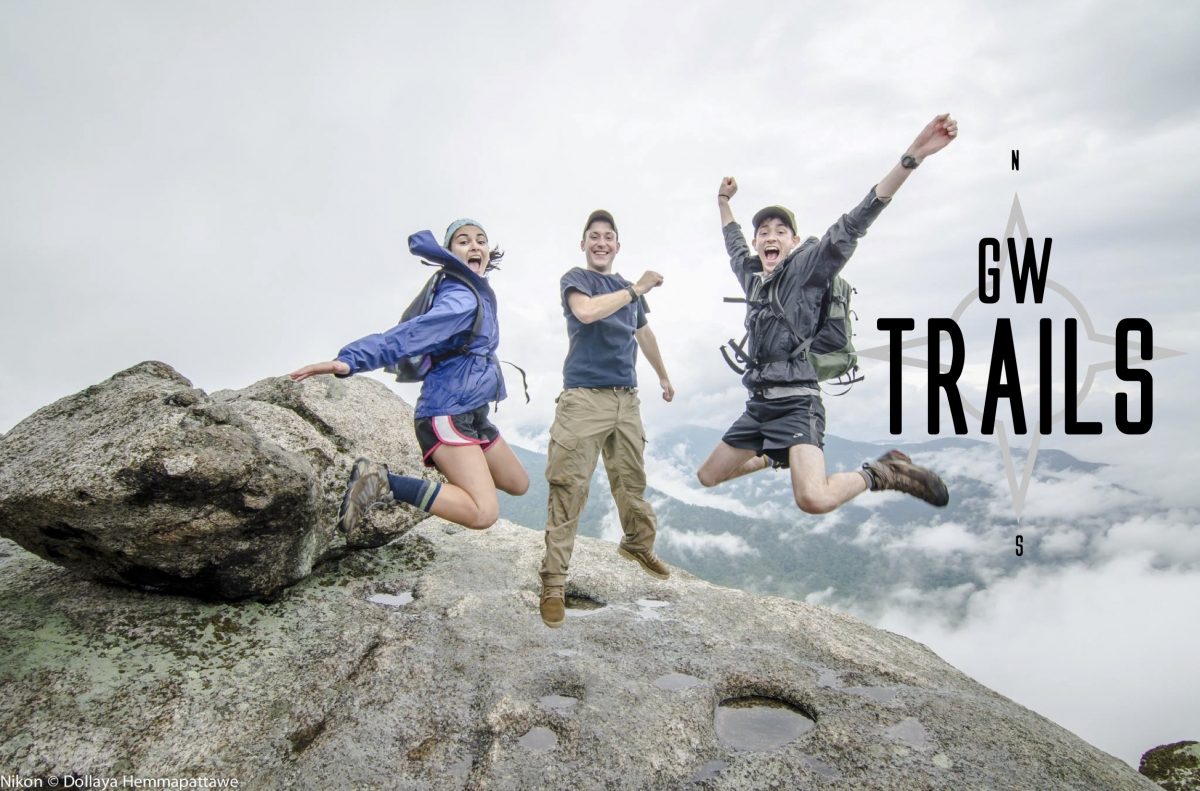 Three students jump for joy on a mountain. - GW TRAILS