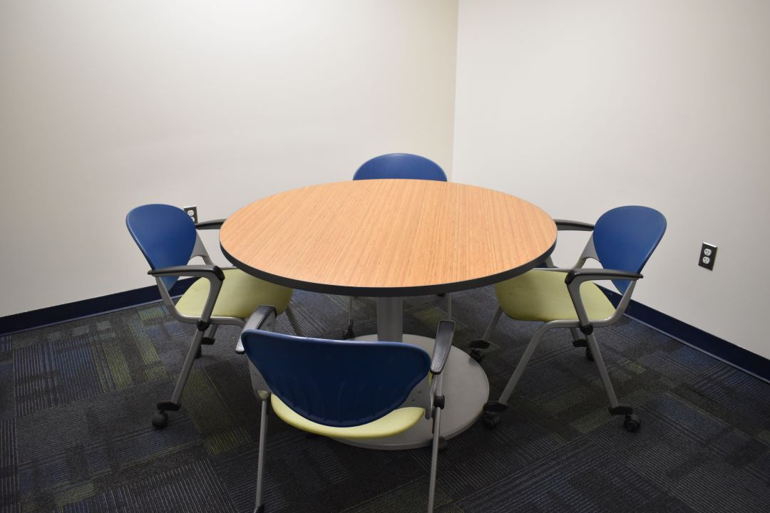 Round huddle table with four chairs around it