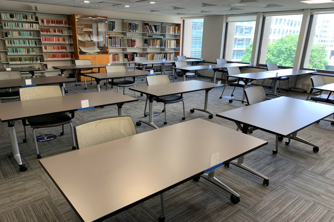Library study room with four rows of four tables each and one chair at each table