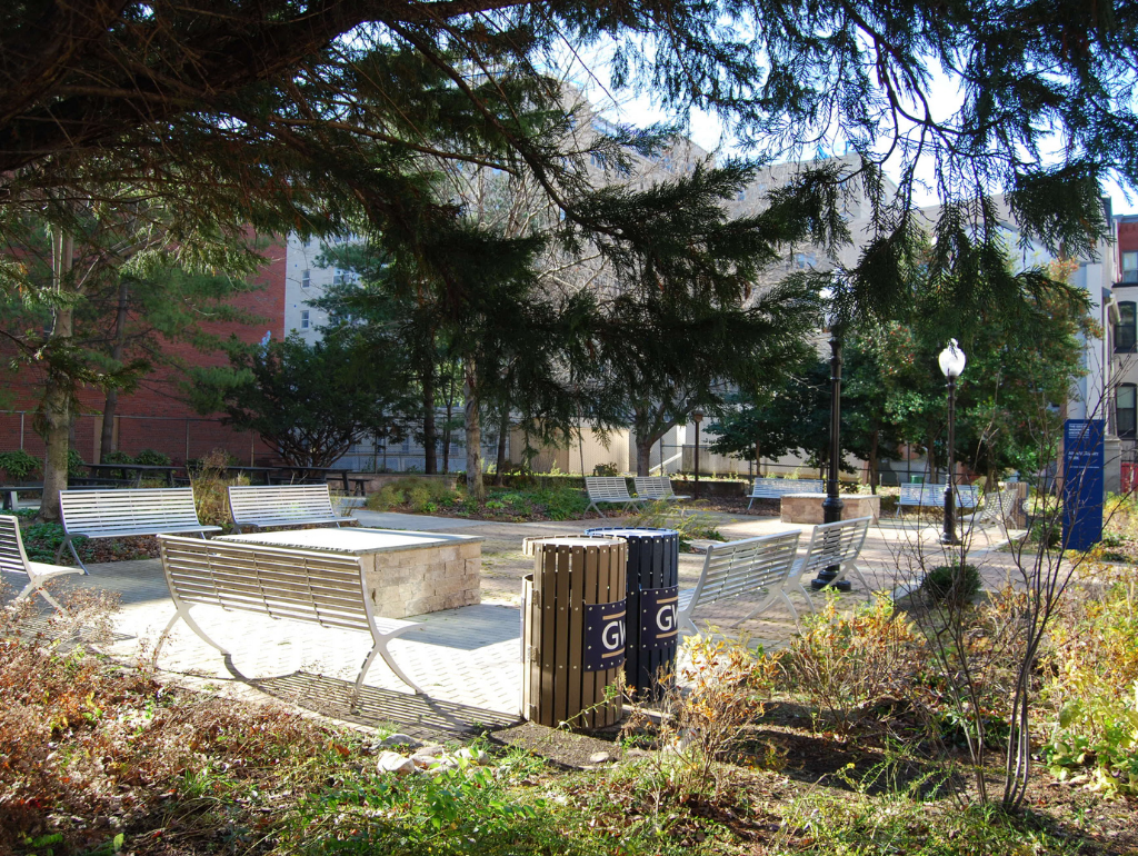 Anniversary Park with metal benches in a rectangular arrangement and trees surrounding