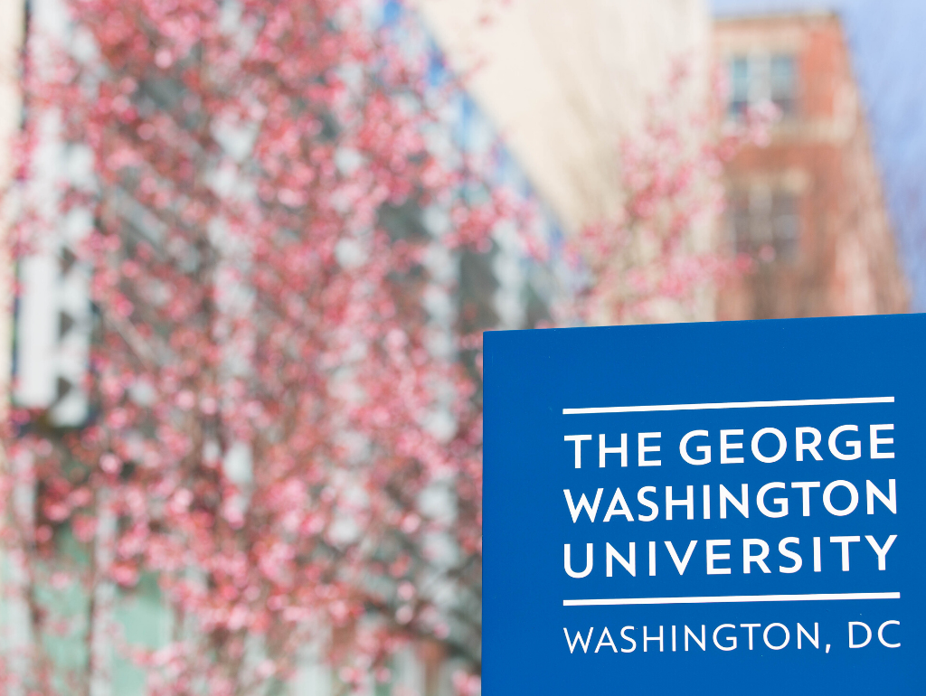 GW sign outside of the Marvin Center and a cherry blossom tree in the background