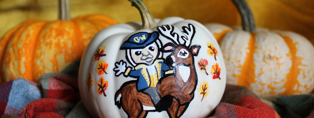Mini pumpkin painted with GW George mascot riding a deer