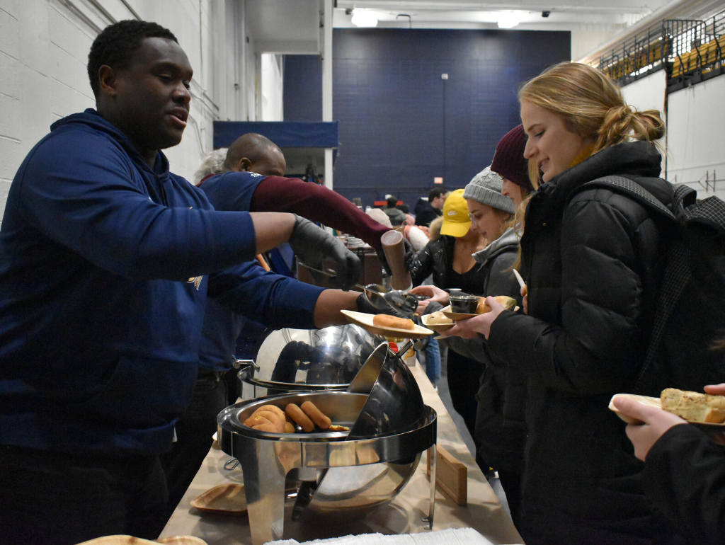A Midnight Breakfast volunteer serving donuts to a student