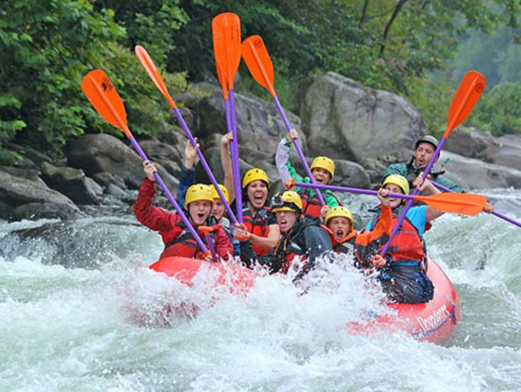 Students whitewater rafting down a river.