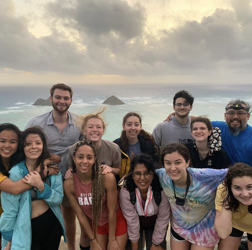 Trails Students in Hawaii after hiking, view of mountains and ocean in the background.