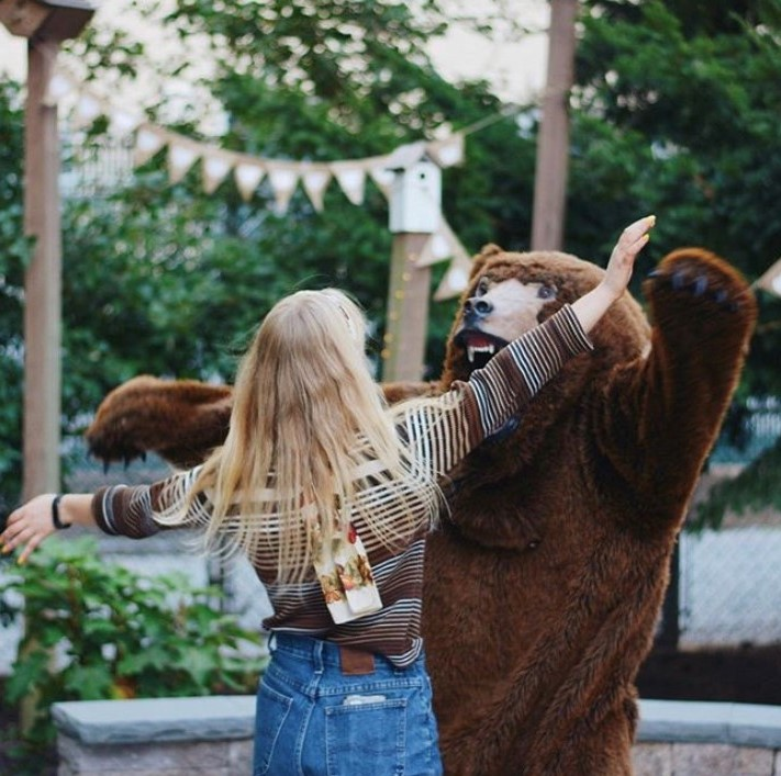 Trails guides at a celebrate for welcoming new student guides. A woman pictured hugging a person in a bear suit.