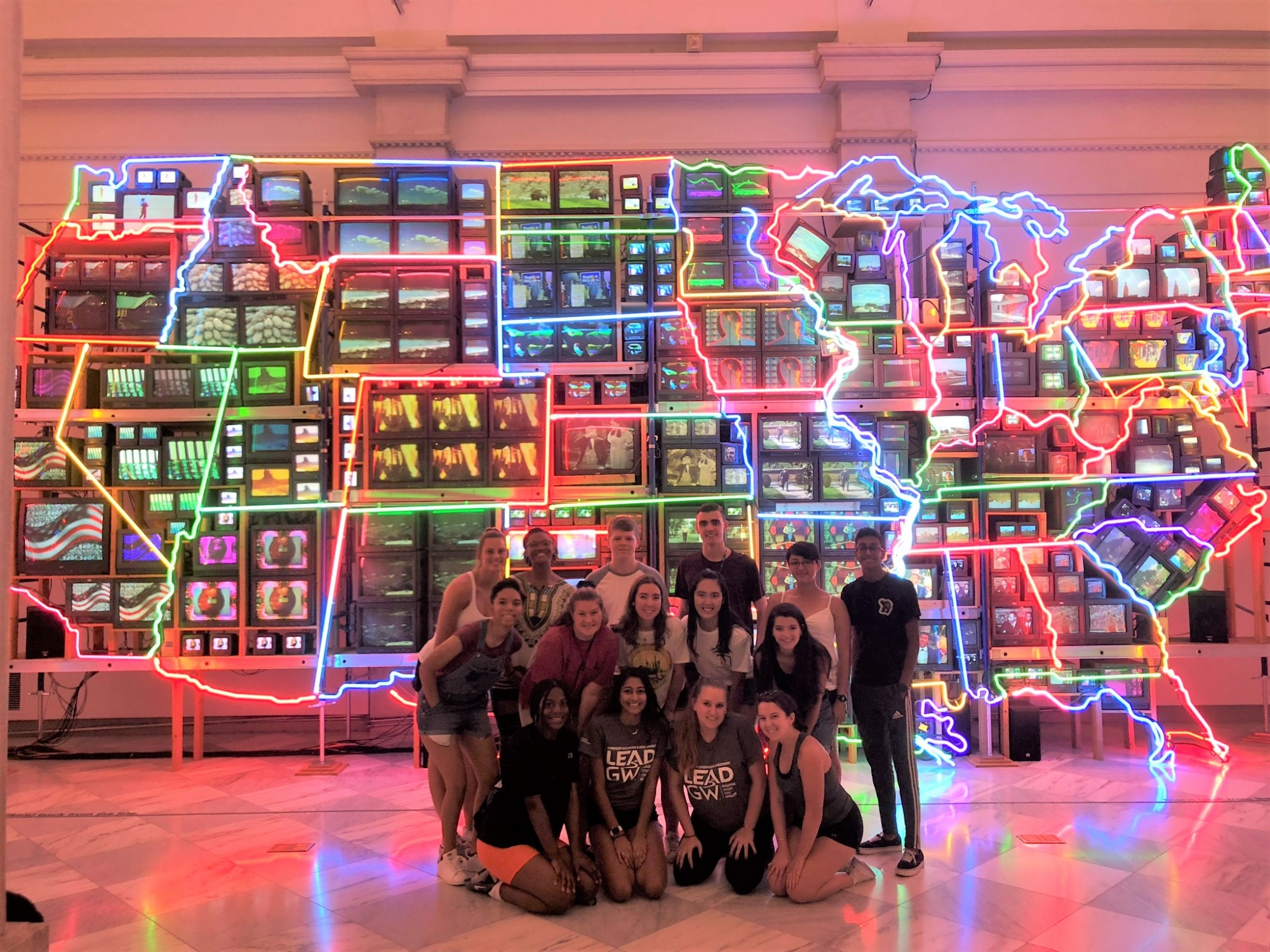 Photo of LEAD guides and incoming students in front of a neon map of the US at a museum.