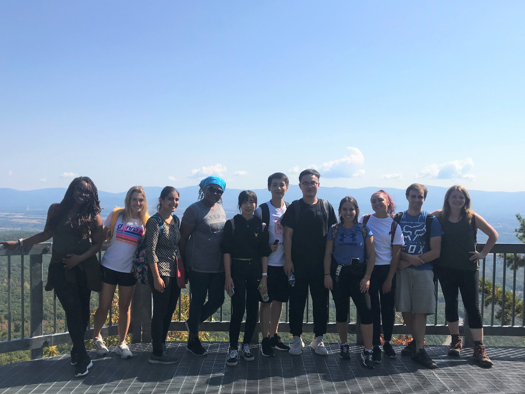 GW students posing for a photo at the top of a mountain at a lookout point.